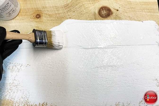 Première couche de peinture blanche Fusion sur la table en pin brut